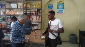 個人経営のスーパーマーケットにバオバブパウダーをPRする専門家と組合メンバー